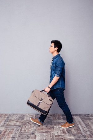 side pose: Full length portrait of a youg asian man walking in jeans wear and bag