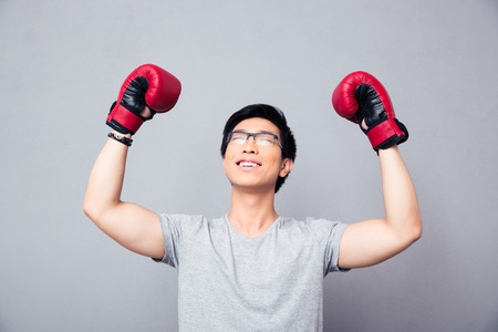 rejoices: Asian man in boxing gloves rejoices victory over gray background Stock Photo