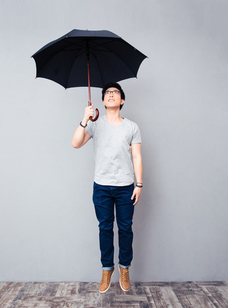 Full length portrait of asian man standing with umbrella Stock Photo