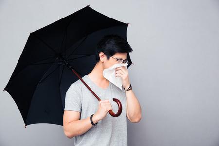 Zieke Aziatische man bedrijf paraplu en waait neus over grijze achtergrond