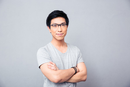 wearing: Portrait of a smiling asian man in glasses standing with hands crossed over gray background. Looking at camera
