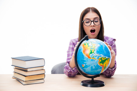 shoked: Amazed young female student sitting at the table and looking at globe over white background