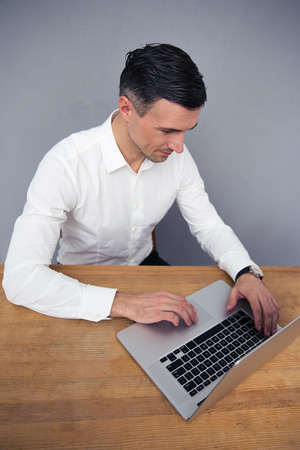 concetrated: Handsome businessman sitting at the table and using laptop