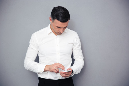 formal wear: Confident businessman in formal wear using smartphone over gray background