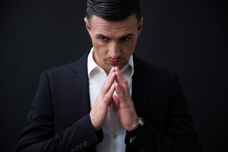 Portrait of a handsome businessman in formal wear praying over black background photo