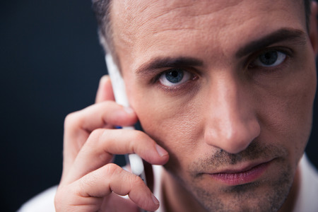 phonecall: Closeup portrait of a handsome businessman talking on the phone and looking at camera