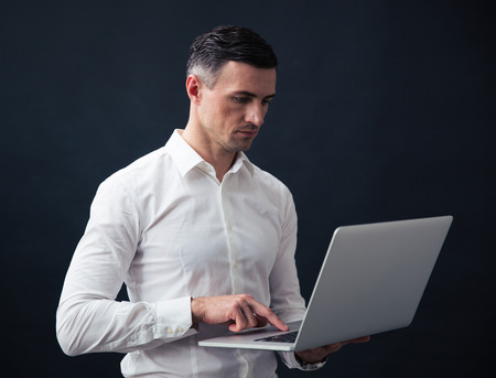 concetrated: Serious businessman standing and using laptop over black background