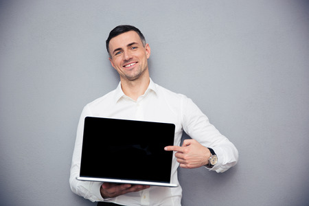 dedo: Hombre de negocios sonriente que se�ala el dedo en la pantalla del port�til en blanco sobre fondo gris. Mirando a la c�mara