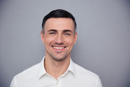 a portrait: Portrait of a happy young businessman looking at camera over gray background Stock Photo