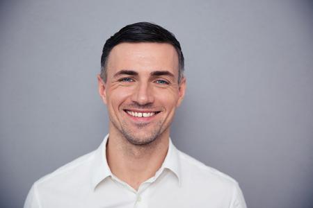 ejecutivos: Retrato de un joven hombre de negocios feliz mirando a la cámara sobre fondo gris