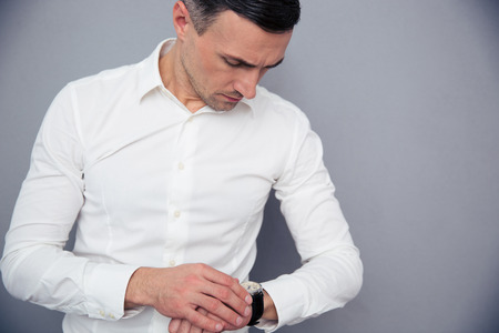 Businessman looking on wristwatch over gray background