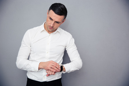 cut wrist: Portrait of a pensive businessman with wristwatch standing over gray background and looking away Stock Photo
