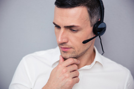 teleconference: Portrait of a pensive male operator over gray background