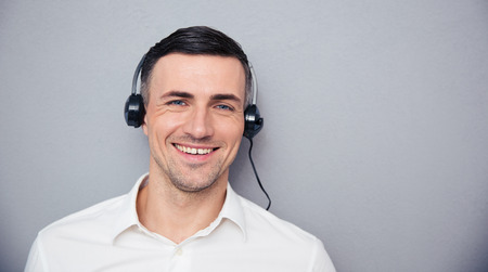 teleconference: Portrait of a smiling male assistant in headphones looking at camera over gray background Stock Photo