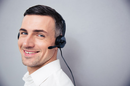 servicio al cliente: Hombre de negocios alegre en los auriculares de pie sobre el backgorund gris y mirando a la cámara