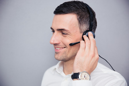 teleconference: Happy businessman with headphones standing over gray backgorund and looking away