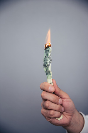 us dollar bill: Male hand holding a burning US dollar bill over gray background