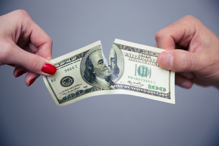 Concept image of a female and male hand dividing money over gray background photo