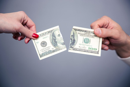 Concept image of a female and male hand dividing money over gray background