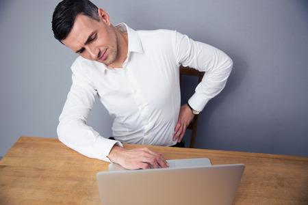 person sitting: Hombre de negocios sentado en la mesa y tiene dolor de espalda