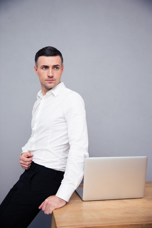 concetrated: Businessman leaning on the table with laptop and looking away