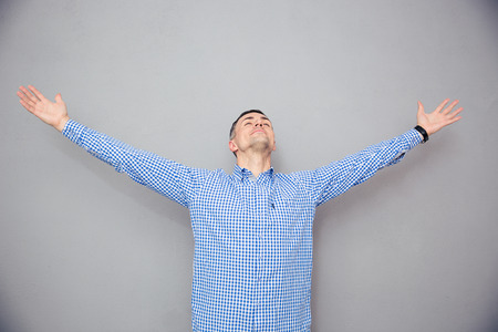 glorify: Portrait of a man gesturing freedom expression over gray background