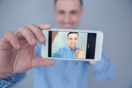 making up: Smiling man showing thumb up and making selfie photo on smartphone Stock Photo