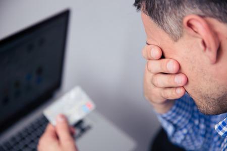 Zdenerwowany mężczyzna posiadania karty kredytowej z laptopa na tle Zdjęcie Seryjne