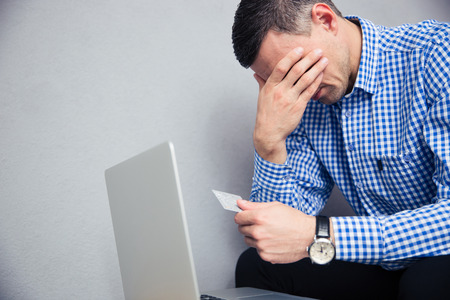 creditor: Upset man holding credit card over gray background