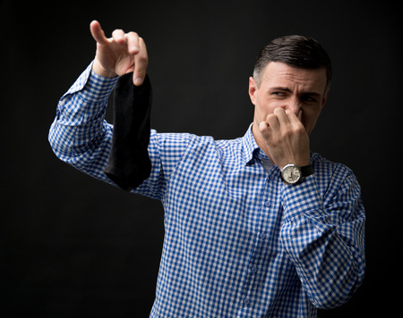 smelly: Man holding smelly socks and clogged nose over black background