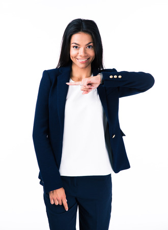 looking away from camera: Smiling young businesswoman pointing finger away over white background and looking at camera