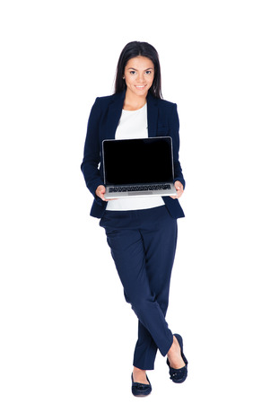 Full length portrait of a happy businesswoman showing blank laptop screen over white background.  Stock Photo