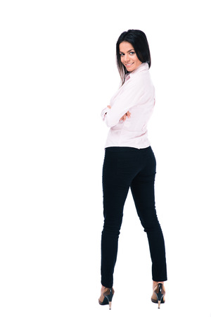 legs folded: Back view portrait of a happy businesswoman standing isolated on a white background and looking at camera