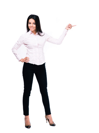 finger pointing: Full length portrait of a cheerful businesswoman pointing finger away. Isolated on a white background. Looking at camera Stock Photo