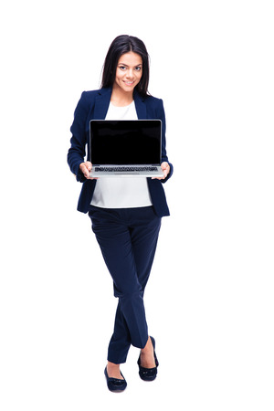 Full length portrait of a smiling businesswoman showing blank laptop screen.  photo
