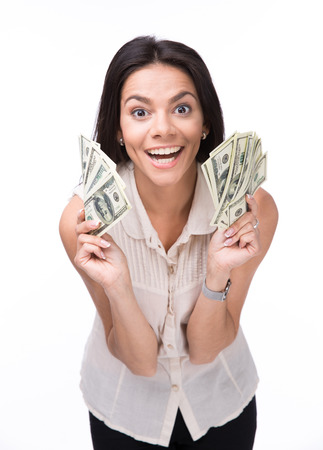 woman holding money: Laughing young woman holding money over white background and looking at camera Stock Photo