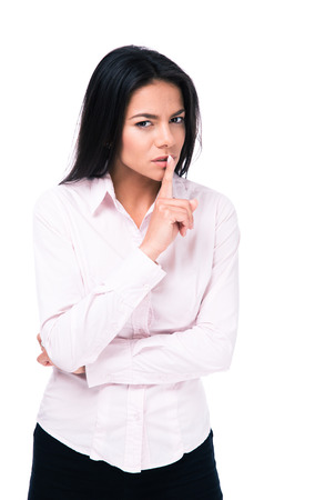 hushed: Businesswoman making silence sign isolated on a white background and looking at camera
