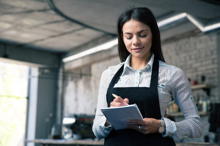 dinners: Happy beautiful female waiter in apron writing order Stock Photo