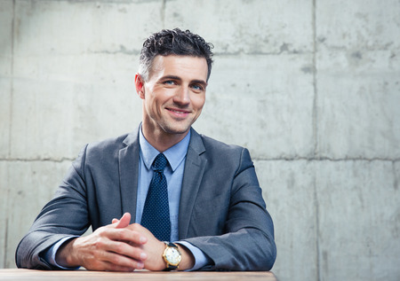 formal portrait: Smiling businessman sitting at the table and looking at camera over conrete wall