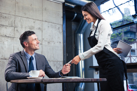 paying: Happy man giving bank card to smiling female waiter in restaurant