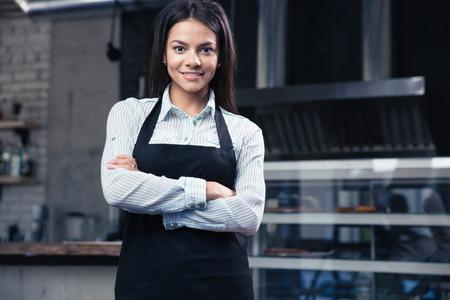 mandil: Camarero femenina encantadora feliz en el delantal de pie con los brazos cruzados en el restaurante y mirando a la cámara Foto de archivo