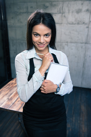 dinners: Smiling beautiful female waiter in apron standing with notepad and pen in cafe. Looking at camera Stock Photo