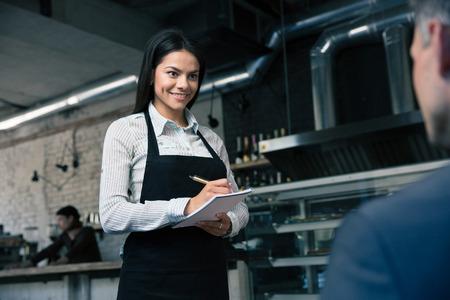 camarero: Camarero femenino feliz en delantal para escribir en el restaurante