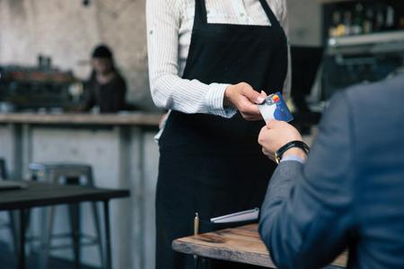 Imagen del primer de una tarjeta de crédito hombre que da al camarero en la cafetería Foto de archivo