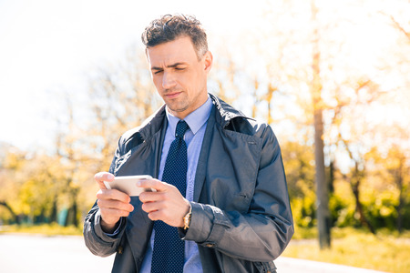 concetrated: Confident businessman in suit using smartphone outdoors Stock Photo