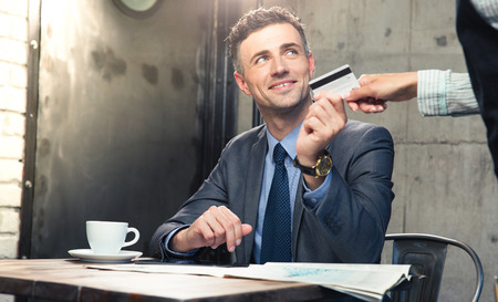 waiter: Handsome man giving bank card to waiter in cafe