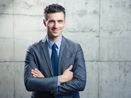 fold: Portrait of a smiling handsome businessman with arms folded over concrete wall