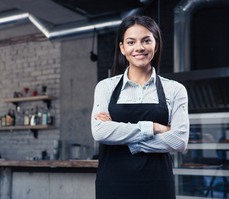serving: Happy cute female waiter in apron standing with arms folded in cafe