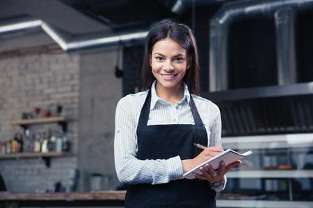 Camarero femenina encantadora feliz en el delantal de la escritura orden y mirando a la cámara