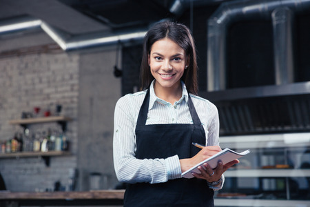 mandil: Camarero femenina encantadora feliz en el delantal de la escritura orden y mirando a la cámara